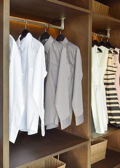 Rangée de chemises blanches et grises suspendues dans une armoire en bois