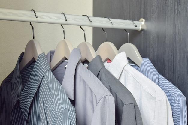 Rangée de chemises noires et blanches suspendues dans une armoire