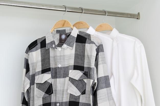 Rangée de chemises suspendues sur un cintre dans une armoire blanche