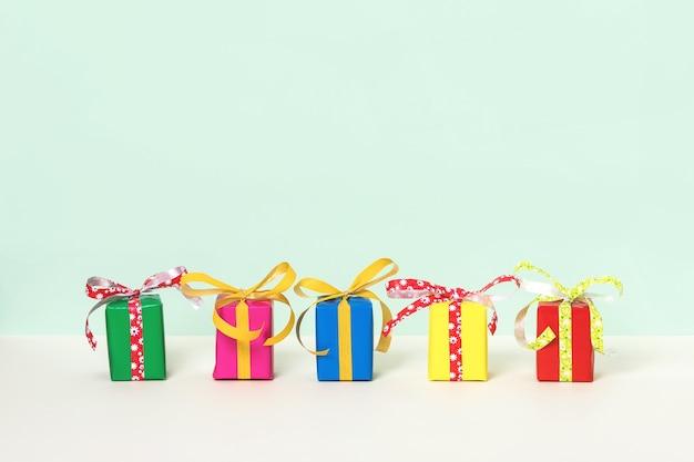 Rangée avec cinq coffrets cadeaux colorés sur fond pastel.