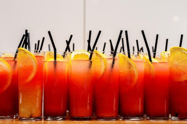Une rangée de cocktails d'agrumes dans des tubes en verre avec des tubes noirs.