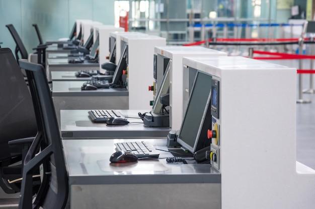 Rangée de comptoirs d'enregistrement vides avec des écrans d'ordinateur à l'aéroport.