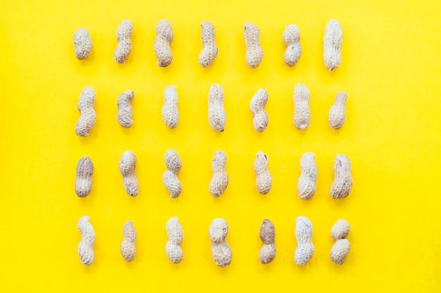 Rangée de coques de cacahuètes sur fond jaune