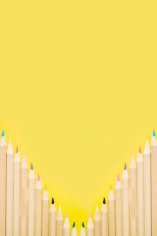 Rangée de crayons colorés sur fond jaune