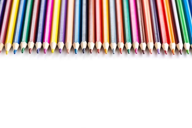 Une rangée de crayons de couleur sur fond blanc