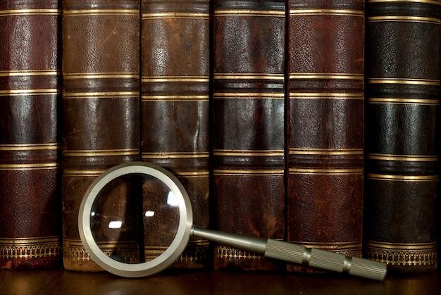 Rangée de dos de livres anciens en cuir usé avec gaufrage or et loupe