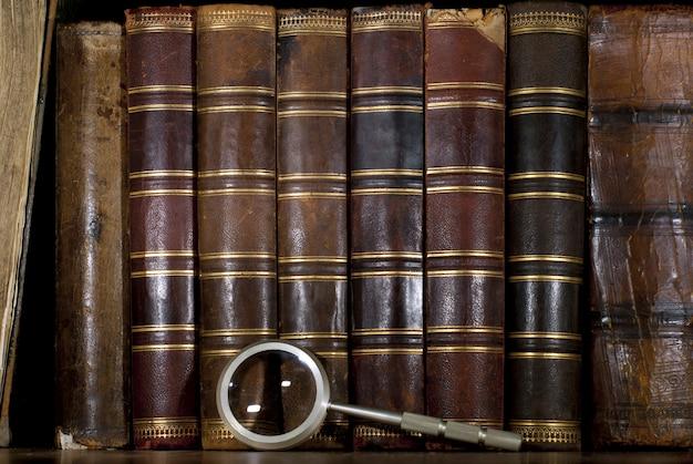 Rangée de dos de livres anciens en cuir usé et une loupe