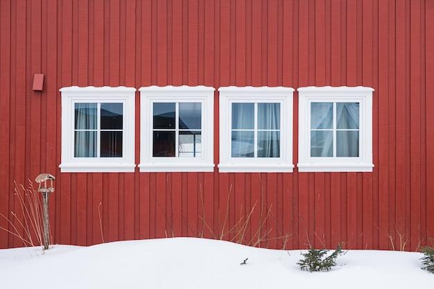 Rangée de fenêtres blanches avec mur en bois rouge et neige
