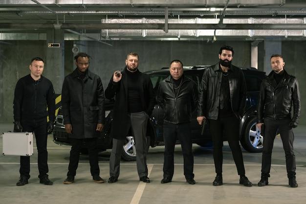 Rangée de gangsters armés interculturels ou de criminels en vestes noires et jeans debout devant la caméra sur l'aire de stationnement