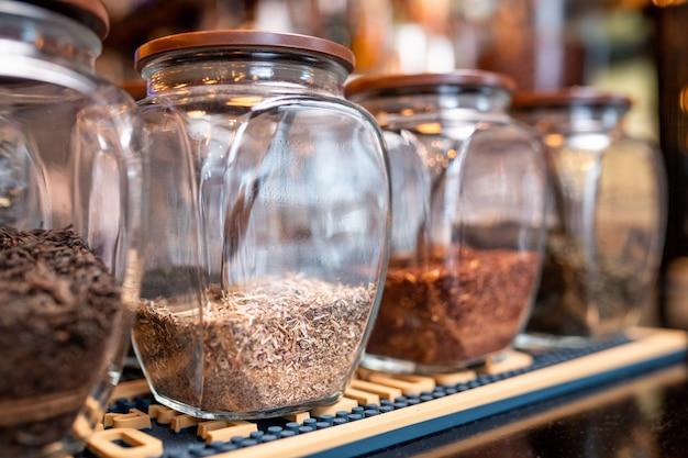 Rangée de grands pots avec assortiment de thé rooibos noir, blanc, vert et debout sur une étagère dans un café ou un restaurant contemporain