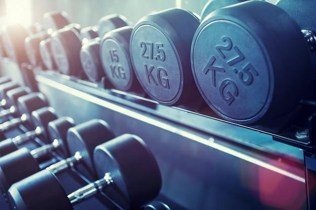 Rangée d'haltères dans la salle de gym. fond de remise en forme.