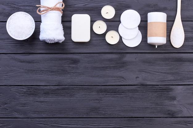Rangée horizontale d'accessoires de spa blancs sur un bureau en bois foncé. serviette avec du savon et des bougies. copiez l'espace, fond de bois sombre.