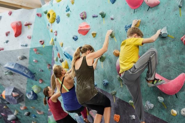 Rangée de jeunes sportives et écolier en vêtements de sport rampant sur le mur d'escalade tout en tenant par de petits rochers