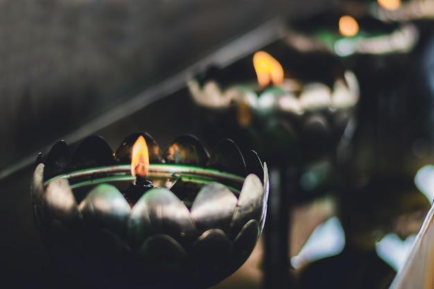 Une rangée de lampes à pétrole allumées dans un temple thaïlandais