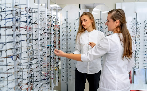 Rangée de lunettes chez un opticien. boutique de lunettes. tenez-vous avec des lunettes dans le magasin d'optique. une femme ophtalmologiste donne des lunettes à une cliente.