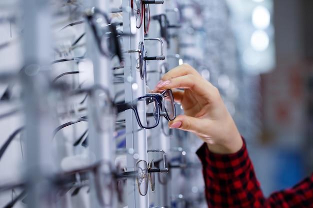 Rangée de lunettes chez un opticien. boutique de lunettes. tenez-vous avec des lunettes dans le magasin d'optique. la main de la femme montre des lunettes