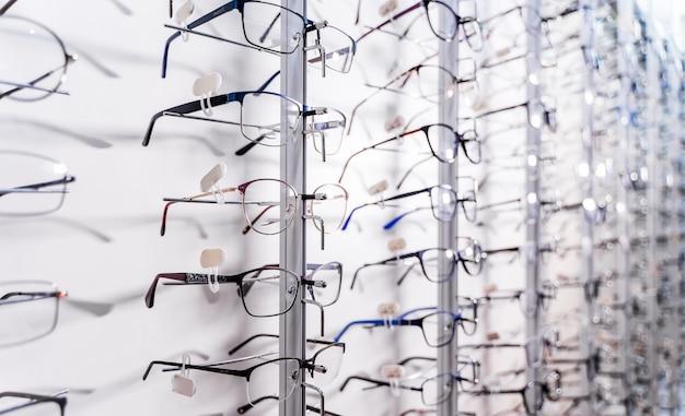 Rangée de lunettes chez un opticien. boutique de lunettes. tenez-vous avec des lunettes dans le magasin d'optique. vitrine avec lunettes en magasin ophtalmique moderne. fermer.