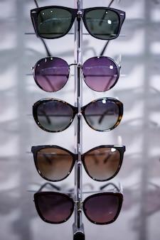 Une rangée de lunettes pour se protéger du soleil. points de stockage. stand avec des lunettes de soleil dans le magasin d'optique. la main féminine montre des lunettes. présentation des points. fermer