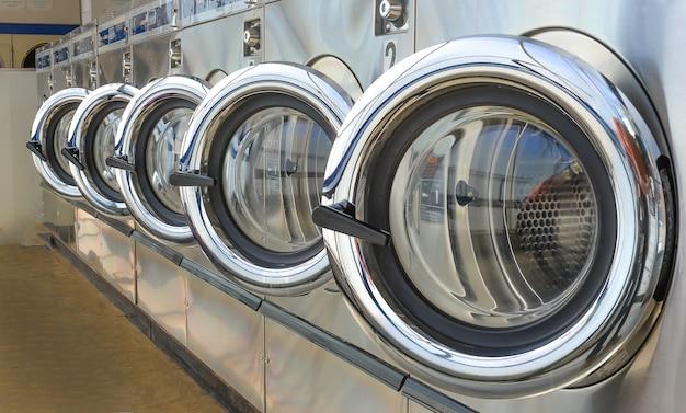 Rangée de machines à laver industrielles dans une laverie automatique.