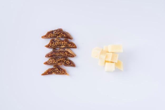 Rangée de morceaux de savoureuse figue séchée et tas de morceaux de fromage pecorino sur fond blanc