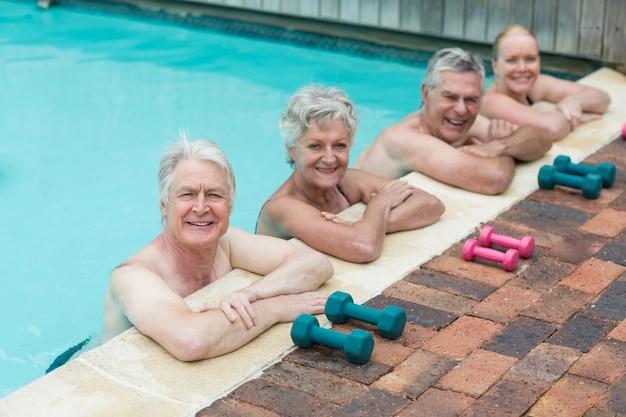 Rangée de nageurs se penchant par des haltères au bord de la piscine