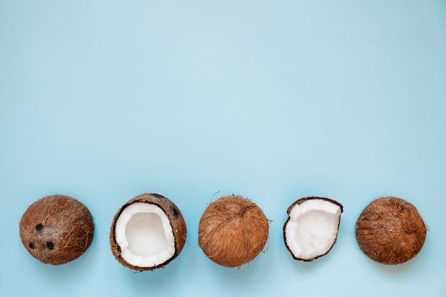 Rangée de noix de coco mûres et ouvertes sur bleu
