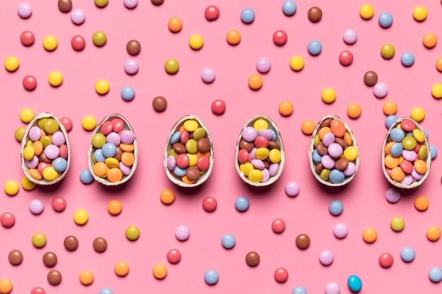 Rangée d'oeufs de pâques cassés avec des bonbons gem sur fond rose
