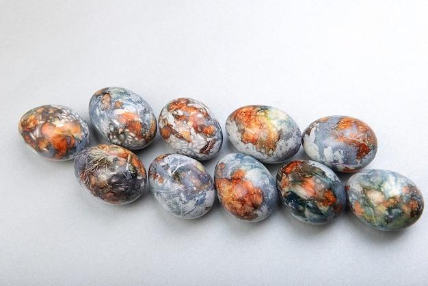 Rangée d'oeufs de pâques colorés peints en produits naturels bleuets et pelures d'oignon, isolé sur une surface grise