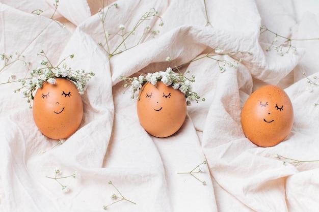 Rangée d'oeufs de pâques avec des couronnes de fleurs décoratives entre textile