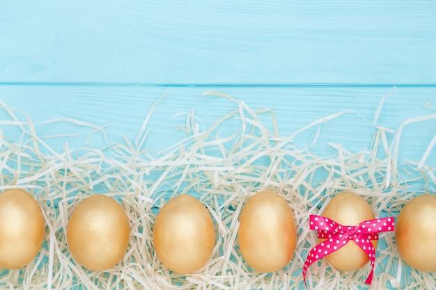 Rangée d'oeufs de pâques dorés décorés de ruban rose sur fond bleu. mise à plat, gros plan.