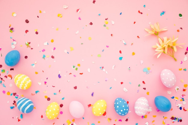 Rangée d'oeufs de pâques entre des confettis brillants