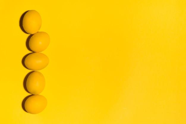 Rangée d'oeufs de pâques jaunes sur une table jaune