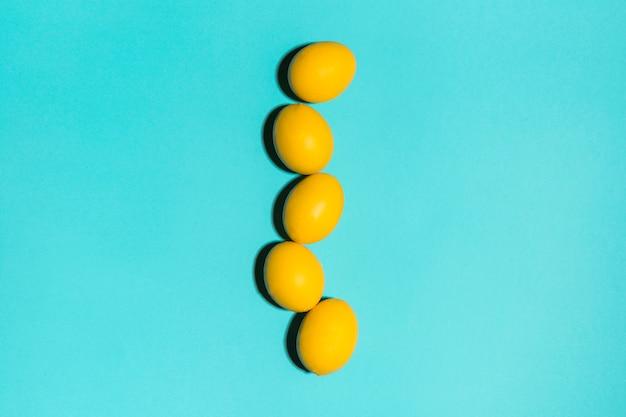 Rangée d'oeufs de pâques jaunes sur la table