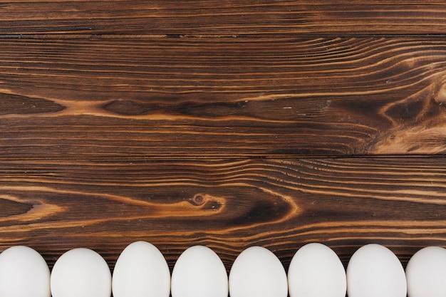 Rangée d'oeufs de poule blanche sur une table en bois marron