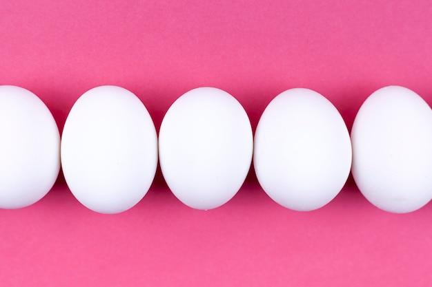 Rangée d'oeufs de poule blancs sur table rose