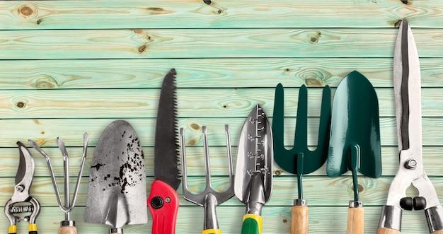 Rangée d'outils de jardinage sur fond de bois
