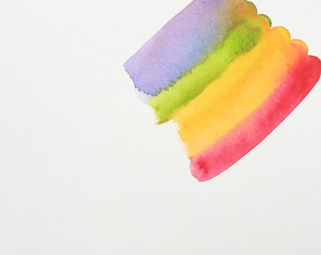 Rangée de peintures violettes, vertes, jaunes et rouges sur papier blanc