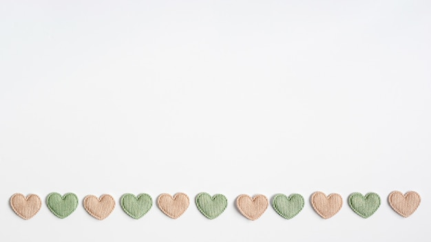 Rangée de petits coeurs textiles à rayures vertes et beiges sur fond blanc