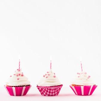 Rangée de petits gâteaux frais avec des bougies allumées sur fond blanc