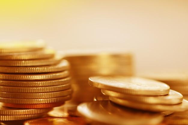 Rangée de pièces sur fond bois pour finances et concept d'épargne, investissement, couleur or