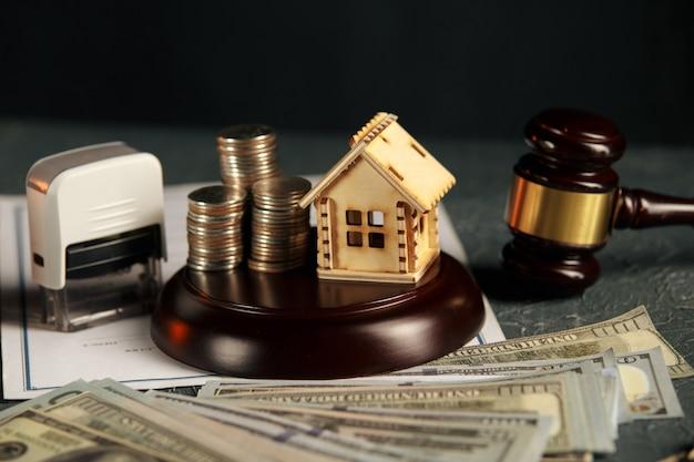 Une rangée de pièces sur un modèle de petite maison et un marteau de vente aux enchères de la loi