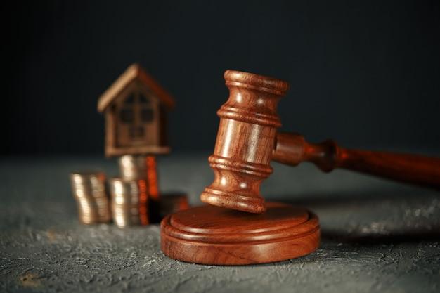 Une rangée de pièces sur un modèle de petite maison et un marteau de vente aux enchères.