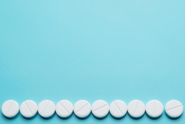 Une rangée de pilules blanches sur un fond bleu.