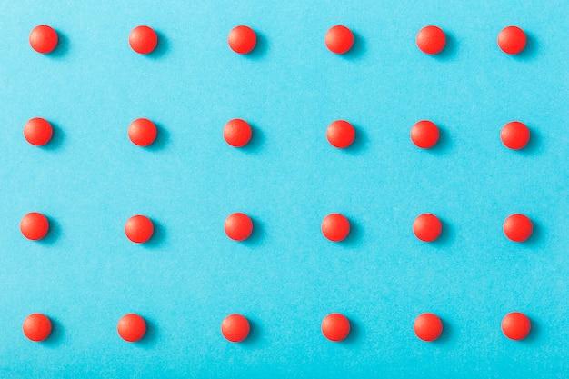Rangée de pilules rouges sur le fond bleu