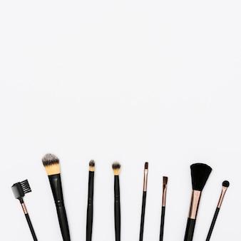 Rangée de pinceaux de maquillage avec espace de copie pour l'écriture du texte sur fond blanc