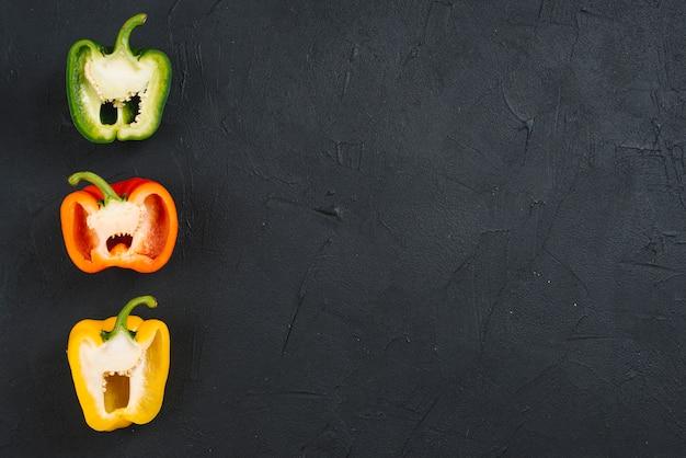 Rangée de poivrons coupés en deux sur fond de béton noir