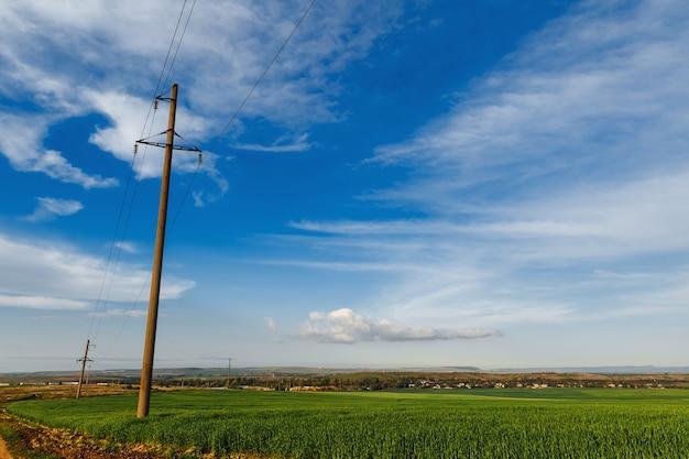 Une rangée de poteaux d'une ligne électrique dans un champ près d'un chemin de terre sous un ciel clair, ligne de transmission d'électricité, alimentation
