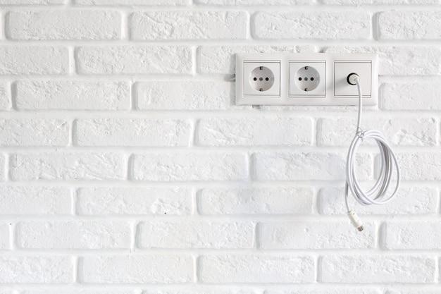 Rangée de prises d'alimentation et de télévision et câble de télévision sur un mur de briques