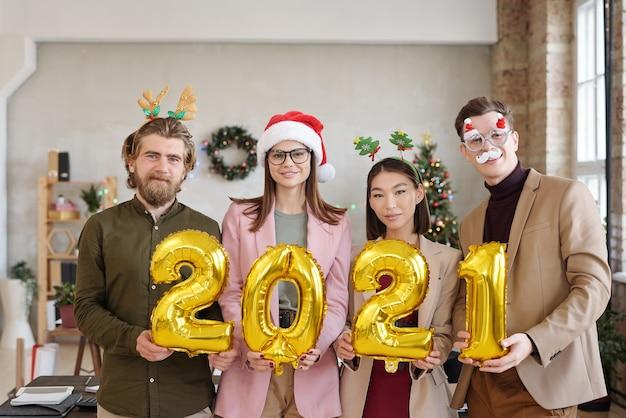 Rangée de quatre jeunes cols blancs interculturels vêtus de vêtements décontractés intelligents et d'accessoires de noël tenant des numéros gonflables de l'année prochaine