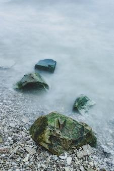 Rangée de rochers dans l'écume des vagues sur la côte de la rivière